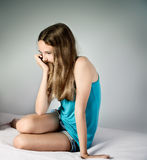 Sad girl sitting on the bed. square Stock Image