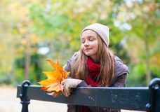 Sad girl sitting on a bench in park Stock Images
