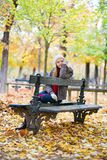 Sad girl sitting on a bench in park Royalty Free Stock Image