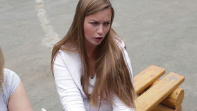 Sad girl sitting on a bench in the street stock footage