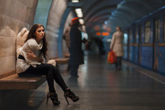 Sad girl sitting. Sad girl sitting on a bench in the subway Royalty Free Stock Photography