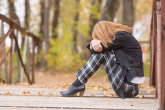 Sad girl sitting on a bridge with her head resting on his knees. Young beautiful girl sitting on a bridge in the warm autumn weather Stock Photos