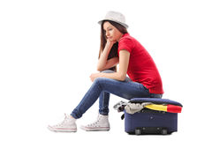 Sad girl sitting on a briefcase full of clothes Stock Image