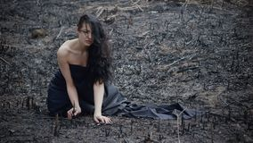 People and dying nature. Ecology concept. Sad girl sitting on the burned-out land. Concept of environmental disaster. Global problems with ecology. Young stock footage