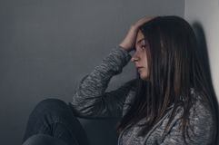Sad girl sitting on the floor in corner of room,  portrait of a. Sad teenage girl looking thoughtful about troubles. Depressed teenage girl. Lonely Depressed Stock Image