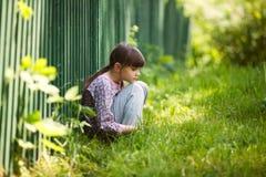 Sad girl sitting on the grass Royalty Free Stock Image
