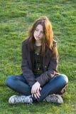 Sad girl sitting on the grass Royalty Free Stock Photo