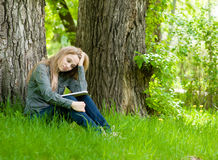 Sad girl sitting on grass and reading a book Stock Photos