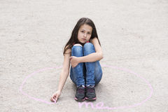 Sad girl sitting on the ground in a circle Stock Photo