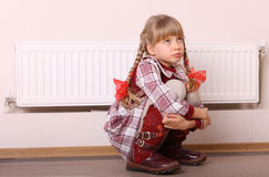 Sad girl sitting near heater. Children problem. Royalty Free Stock Images