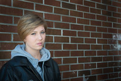 Sad girl sitting outside brick wall in school yar Royalty Free Stock Images