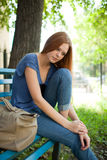 Sad girl sitting on a park bench Stock Images