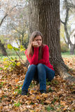 Sad girl sitting in a park Royalty Free Stock Photo