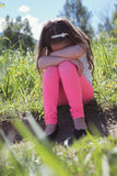 Sad girl sitting in parkland. On a sunny day Royalty Free Stock Photo