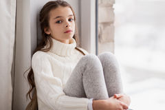 Sad girl sitting on sill at home window in winter Royalty Free Stock Images