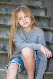 Sad girl sitting on the stairs. Portrait of a sad little girl sitting on the stairs Stock Image