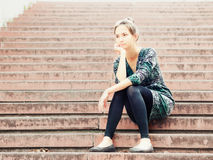 Sad girl sitting on steps. Sad lonely young woman sitting on steps. Portrait of serious girl with facial expression outdoors Royalty Free Stock Photos
