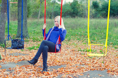 Sad girl sitting on the swing in colorful autumn park Stock Image
