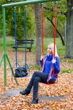 Sad girl sitting on swing in park on colorful autumn day Royalty Free Stock Photos