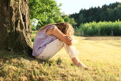 Sad girl sitting by trunk Royalty Free Stock Photo