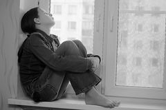 Sad girl sitting on a window sill in depression Stock Photography