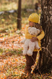 Sad girl standing at the birch in autumn forest and hugs bear toy Stock Images