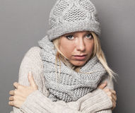 Sad girl staying warm in wrapped up cozy winter scarf Stock Image