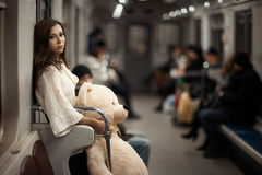 Sad girl in the subway. Sad girl with toy bear in her hands, she in a subway car. Rear people but they are very vague and can not be found. Photo toned Stock Images