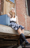Sad Girl with suitcase. Portrait of a teenaged young woman sitting on the steps of a rundown building with her suitcase beside her and a sad expression on her stock photography