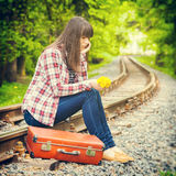 Sad girl with suitcase and bouquet of dandelions sitting on the Royalty Free Stock Images