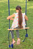 Sad girl on swing. Sad girl with long ponytale in t-shirt with colorful butterflies, grey pants and pink shoes sitting on swing Royalty Free Stock Photo
