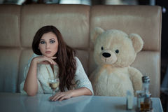 Sad girl at the table with a toy bear. Stock Images