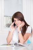 Sad girl talking on the phone at home Stock Photography