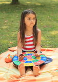 Sad girl with target. Sad sitting little barefoot girl playing with a colorful target Royalty Free Stock Photos
