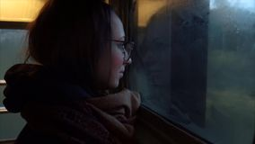 Girl tourist is looking out the window in vestibule train. Sad girl tourist is looking out the window in vestibule train. fast train stock footage