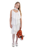 The sad girl with a toy. The sad girl in a white dress with a toy Stock Photo