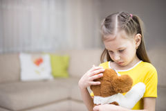 Sad girl with a toy dog Royalty Free Stock Image