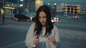 Sad girl trying to fire sparkler with gas lighter, in front of the night city traffic blurred stock footage