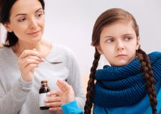 Sad girl turning her face from a mother with helpful medicine Royalty Free Stock Photos