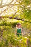 Sad girl under tree. Little blonde girl in green polka dot dress standing under the branches of a tree in Springtime with her eyes cast down Stock Images