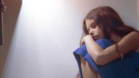 Sad girl upset embraces her feet. is depressed and suicidal little lamentable girl schoolgirl sadness misses the night. Sad girl upset embraces her feet. is stock footage