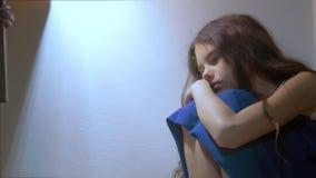 Sad girl upset embraces her feet. is depressed and suicidal little lamentable girl schoolgirl sadness misses the night. Sad girl upset embraces her feet. is stock video footage
