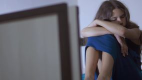 Sad girl upset embraces violence her feet. is depressed and suicidal little lamentable girl schoolgirl sadness lifestyle. Misses the night in bed concept stock footage