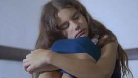 Sad girl upset embraces violence her feet. is depressed and suicidal little lamentable girl schoolgirl sadness misses. The night in lifestyle bed concept stock video footage