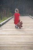 Sad girl walking on wooden path with teddy bear Stock Photography