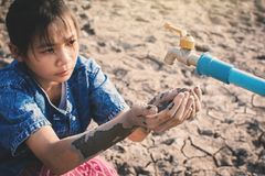 Sad girl want to drink some water on crack ground. Concept drought and shortage of water crisis royalty free stock photo