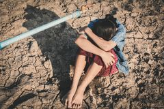 Sad girl want to drink some water on crack ground. Concept drought and shortage of water crisis stock images