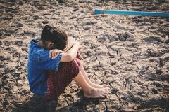 Sad girl want to drink some water on crack ground. Concept drought and shortage of water crisis stock photos