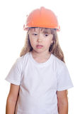 The sad girl in a white undershirt and an orange helmet. The little sad girl in a white undershirt and an orange helmet stock photo