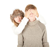 Sad girl in winter hat covering boyfriend's eyes Royalty Free Stock Image